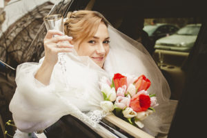 Beautiful blonde bride looking out of limousine window